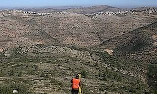 A Palestinian surveyor works at the site where the