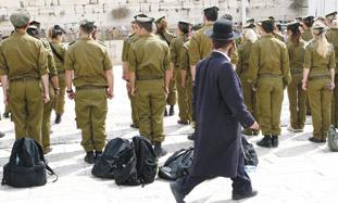 A haredi man walks past IDF soldiers