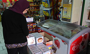 An Arab woman looks at matza in a grocery story in
