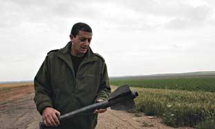 A Sderot security officer examines Gazan rocket