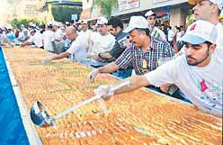 Bakers prepare a giant kunafa in Nablus. The local