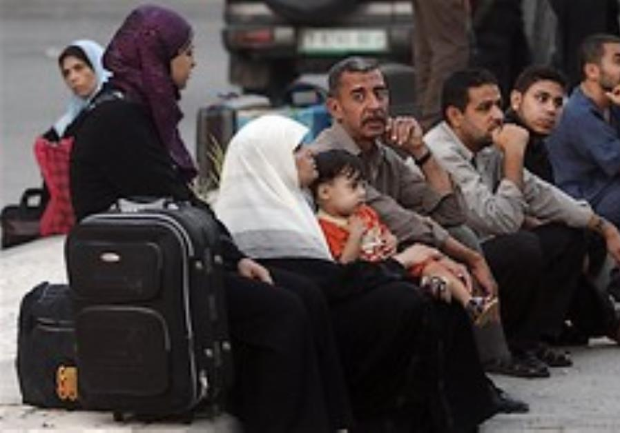 Palestinians wait next to their luggage to leave o