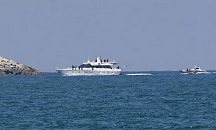 An Israeli armed naval boat, right, escorts a ship