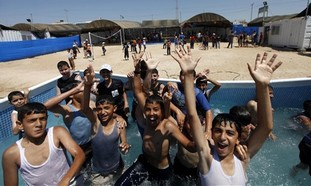 Palestinian boys wave to the camera as they enjoy