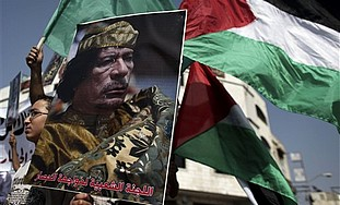 A Palestinian boy holds a poster of Libyan leader