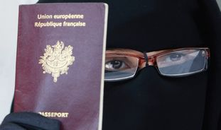A WOMAN holds her passport in a Paris suburb last month.