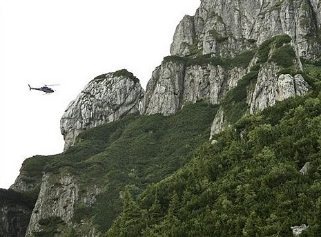 A rescue helicopter hovers in the mountainous area near the Transylvanian town of Bran, Romania, Tue