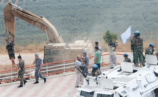 U.N. PEACEKEEPERS on their armored vehicle monitor the area as an Israeli mechanical grabber operate