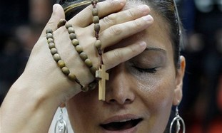 An observant Christian woman, prays as she protests against the airing of a program about Jesus on t