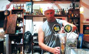 HARRY SHILVOCK pours a beer at the Dancing Camel brewery's bar.