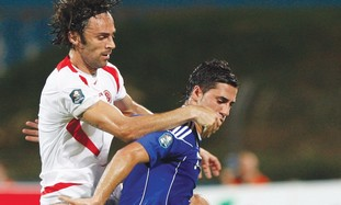 ISRAEL'S BIRAM KAYAL fends off a Malta player.