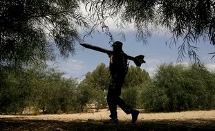 A Palestinian Islamic Jihad man holds a rocket