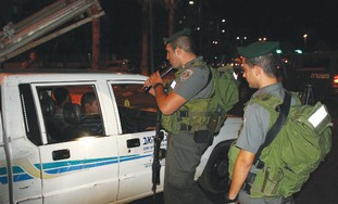 BORDER POLICE personnel examine a vehicle