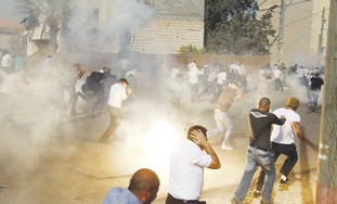 Rioters flee tear gas in the city of Umm el-Fahm