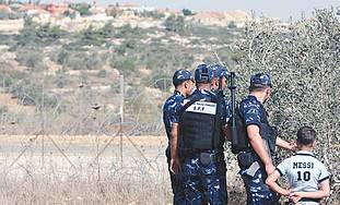 Palestinian police officers by an olive tree