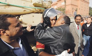 An Egyptian protestor kisses an army officer.