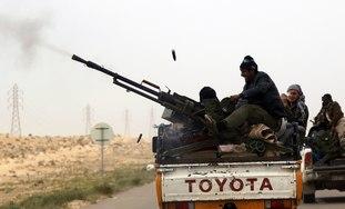A rebel fires his anti-aircraft gun near Benghazi.