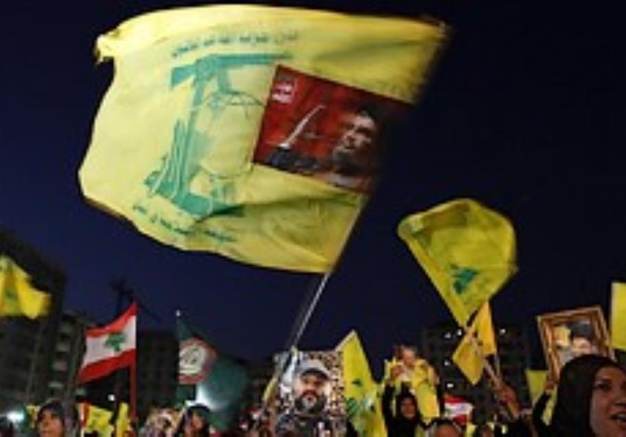 Hizbullah supporters wave Hizbullah flags during a
