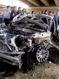 People gather around a destroyed car after a suici