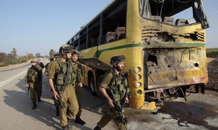 Soldiers walk past the damaged bus on April 7.