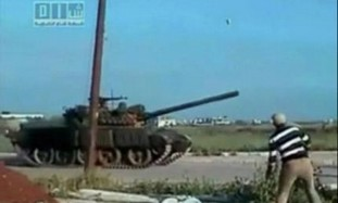 Protester throws rock at tank in Deraa, Syria