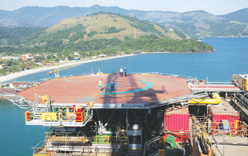 Workers walk on a Petrobras offshore-oil platform