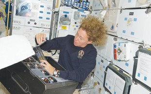 'Atlantis' astronaut secures research from device.