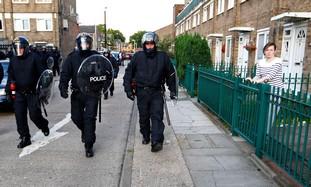 Riot police patrol through an estate in e. London
