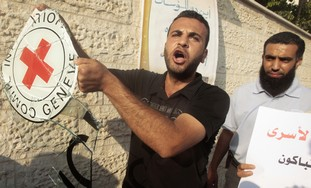 Palestinian holds IRC sign outside Hamas headquart