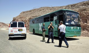 Security personnel next to bus after ambush, Thurs