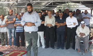 Tuba Zanghariya men pray outside bured mosque