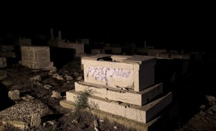 Graffiti is seen on a gravestone in Jaffa cemetery