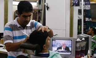 Palestinians in barber shop watch Mahmoud Abbas.