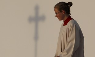Girl stands in Catholic Church.