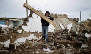 A Turkish man removes rubble after earthquake
