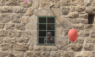 Palestinian woman looks out window in Hebron