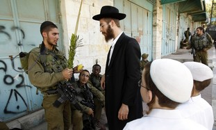 IDF soldier, religious Jews on sukkot, Hebron