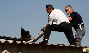 Israeli firefighter and policeman remove Katyusha