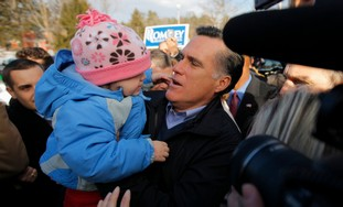 Mitt Romney holds a child at a campaign event