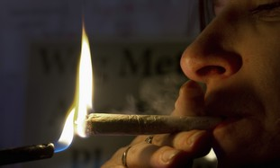 Woman smokes a marijuana cigarette [illustrative]