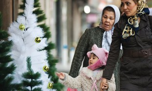 Mother, daughter look at Christmas trees in Tehran