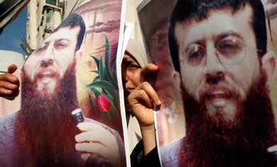 Palestinians holding poster of Khader Adnan