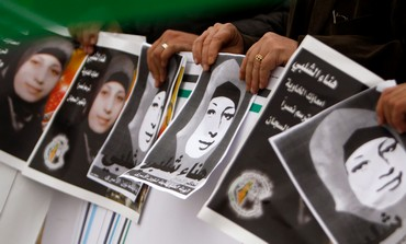 Palestinians hold pictures of Hana Shalabi