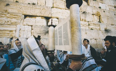 A worshiper holds up a Torah scroll