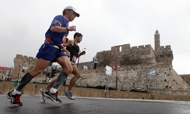 Runners in Jerusalem Marathon pass Old City