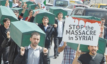 Syrian demonstrators carry mock coffins in Turkey