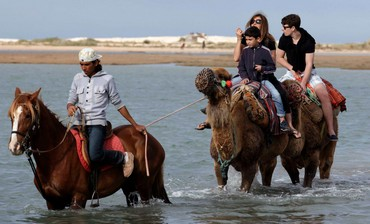 Tourists ride a camel in Djerba, Tunisia