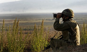 IDF soldier looks into Lebanon near Metula