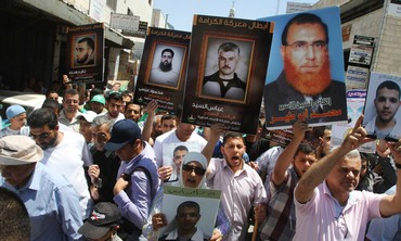 Palestinians in Ramallah hold prisoners' pictures