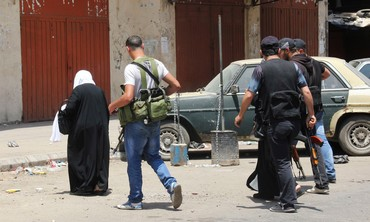 Woman walks past Sunni Muslim gunmen